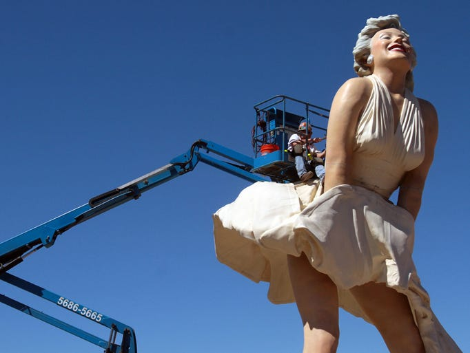 Ted Sitting Crow Garner does some early prep work on Monday, March 31, 2014 to get the Forever Marilyn sculpture ready for dismantling in Palm Springs, Calif. Garner and fellow crew members removed bondo from each of the sculpture's seams and also freed up an access panel on Marilyn's back, which will help them get to the bolts holding the sculpture together. Forever Marilyn is scheduled to be taken apart on Tuesday morning.