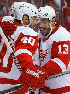 Detroit Red Wings center Pavel Datsyuk, right, celebrates with Henrik Zetterberg (40) after scoring against the Phoenix Coyotes  during an NHL hockey game on Saturday, Oct. 19, 2013, in Glendale, Ariz.