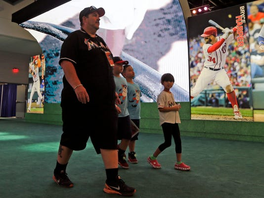 In this Friday, July 7, 2017, photo, fans walk by photo of Washington Nationals' Bryce Harper at the All-Star FanFest at the Miami Beach Convention Center in Miami Beach, Fla. Virtual Reality baseball is a hit at the All-Star FanFest in Miami. Fans get to feel what it's like to be the San Francisco Giants' Buster Posey catching without the pain of snatching major league pitches at 86-to-93 mph. (AP Photo/Alan Diaz)
