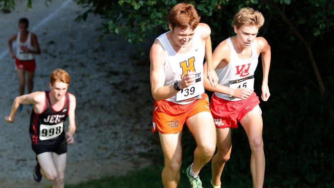 West Lafayette's Evan Johnson, right, marks Harrison's Charlie Brinkerhoff as they crest a hill in the City County Cross Country meet with a time of 16:44 Tuesday, September 1, 2015, at the Tippecanoe Amphitheater. Brinkerhoff hopes to claim the Raiders' mile record to conclude his career before he begins a Mormon mission this summer.