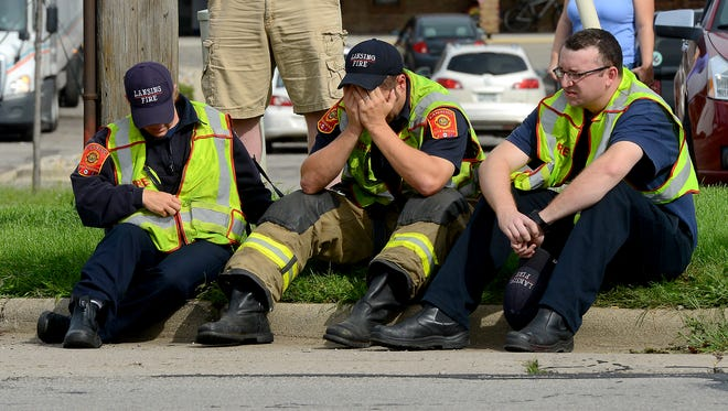 """A Lansing firefighter puts his head in his hands as he and other firefighters sit on the curb on Cedar Street just north of Jolly Road Wednesday, September 9, 2015, after a fellow firefighter was hit by a vehicle during the """"Fill the Boot"""" collection campaign."""