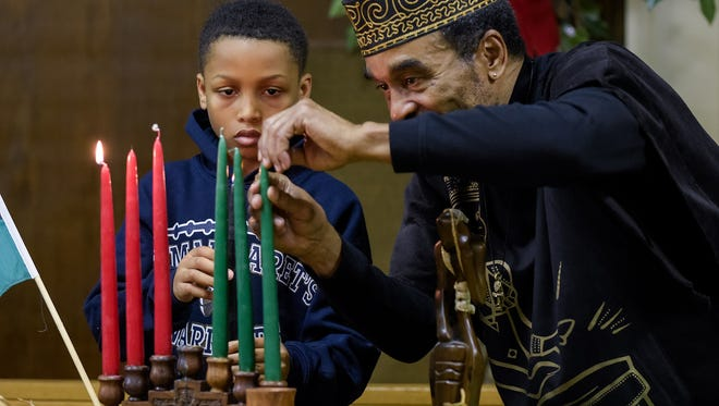 M. Moore, 10, and Baba Kamau Ngon light candles at a Kwanzaa Business Expo at Episcopal Church of Saints Andrew and Matthew in Wilmington on Tuesday.