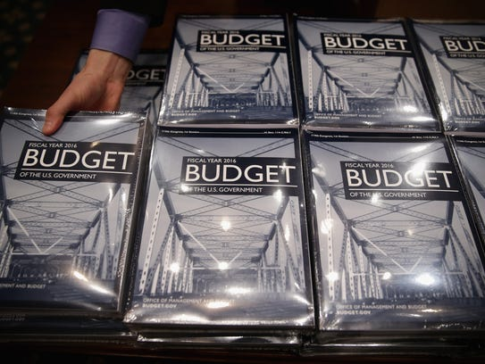 Staffers bring out copies of the president's fiscal