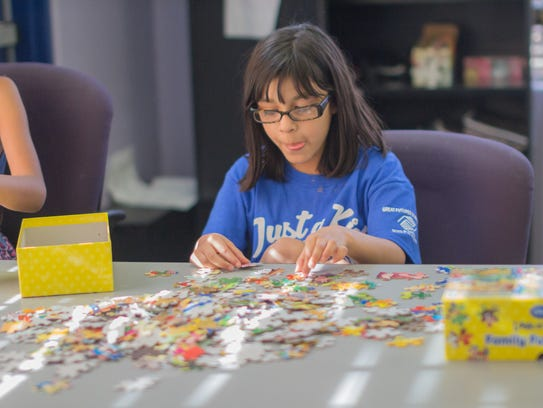 Faith Nino, 9, does a puzzle during free time at the