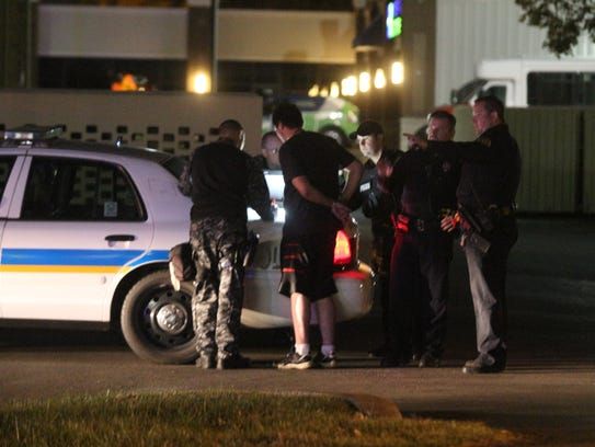 A juvenile in handcuffs at the scene of a fatal shooting