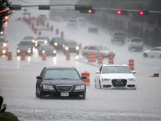 A pair of vehicles stall in flood waters during a heavy