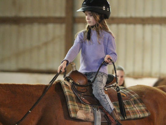 Tammbra Smith, 8, rides her horse around the barn at