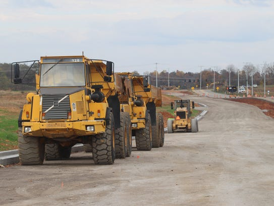 Construction vehicles sit along Rossview Road on the