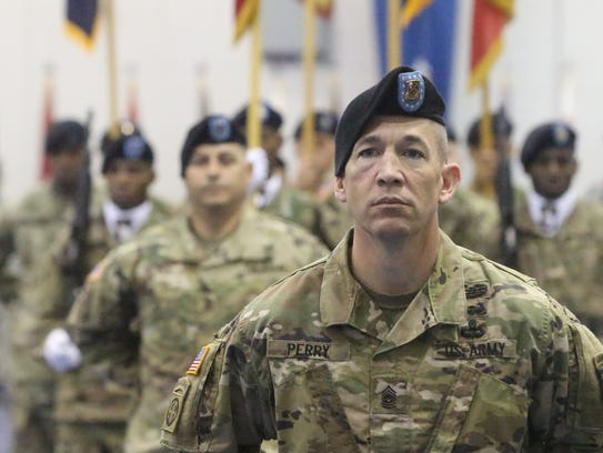 Command Sgt. Maj. Michael J. Perry stands in front
