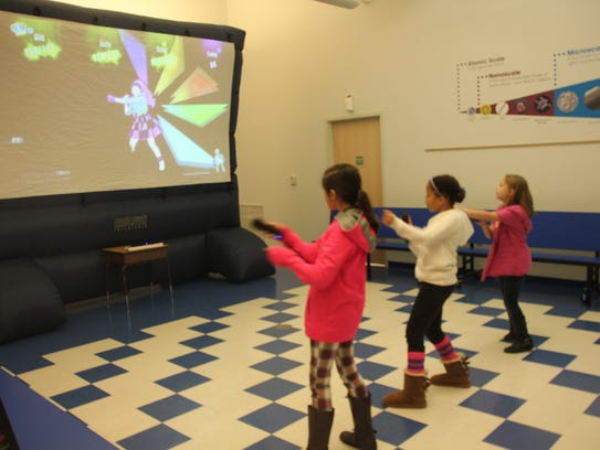 Kids play a video game as part of festivities at the