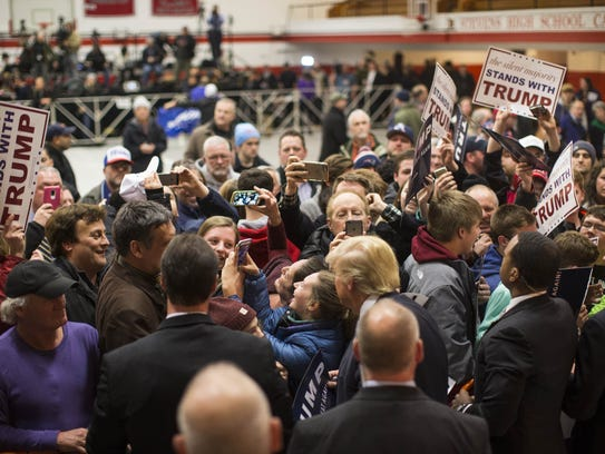 Donald Trump takes a selfie with a supporter after