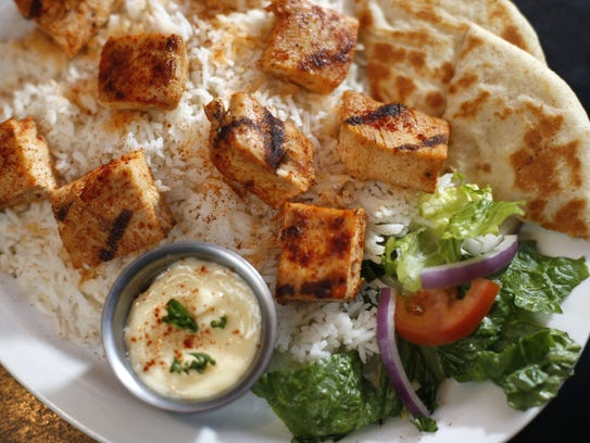 A plate of shish tawook is served over rice at Open