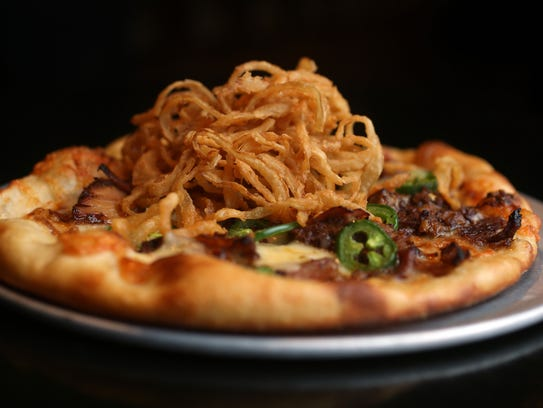 Famished Frog/HOPS craft beer bar Executive Chef Kenny Raymond's BBQ pulled pork with jalapeno and crispy onion gourmet pizza, part of the restaurants gourmet new menu items.