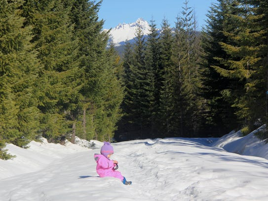 Lucy Urness sits at a view of Three Fingered Jack on