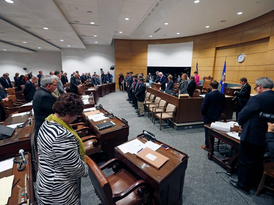 State senators bow during the opening prayer at the
