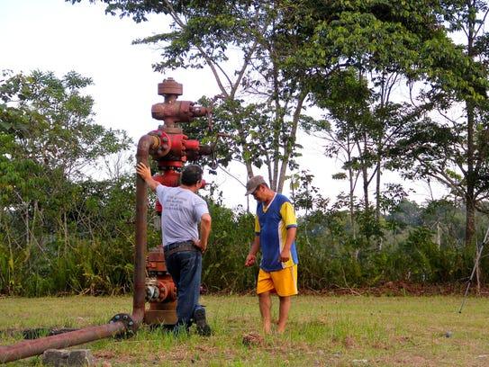 Ecuadorean farmer Jose Aveiga examines an oil well
