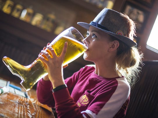 Kelli Johnson of Des Moines drinks beer from a boot