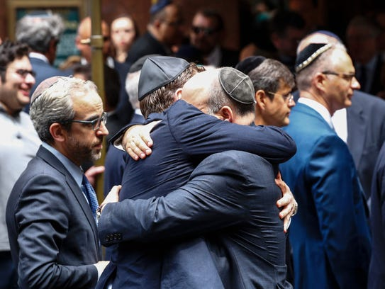 People embrace outside the Fifth Avenue Synagogue during