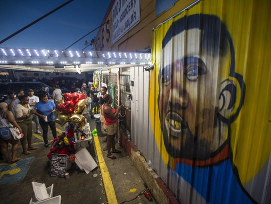 Protesters gather in front of a mural painted on the