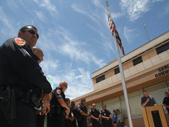 Carlsbad police officers listened during a prayer by