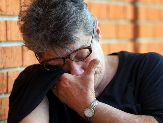 Bertha Stally wipes tears from her face as she talks