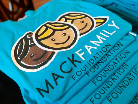 A stack of t-shirts with the logo for the new Mack