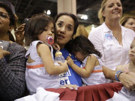 Simpatizante de Hillary Clinton sostiene a sus hijas