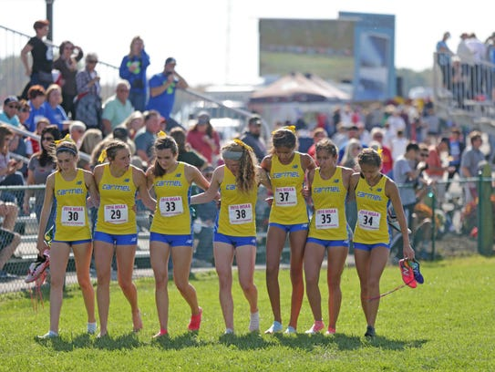 The Carmel Girls Cross Country Team links arms as they