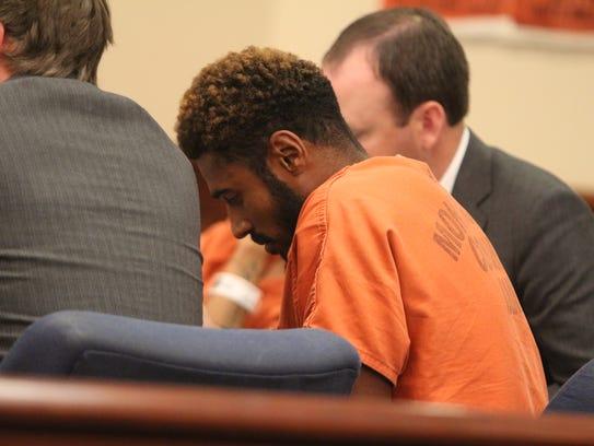 Reginald Pope, center, listens to testimony at a preliminary