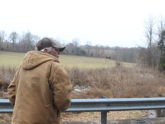 Frank Metcalf on his hay farm, looking over his stream