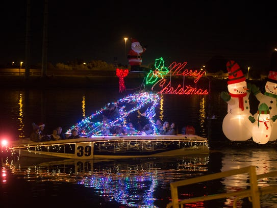 Boats lit up by Christmas lights and decorations make