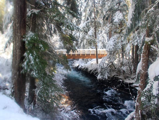 A bridge over the McKenzie River, covered in snow,