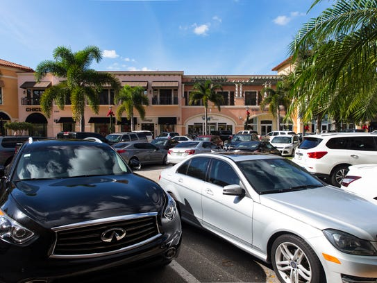 Cars drive through full parking lots at Coconut Point
