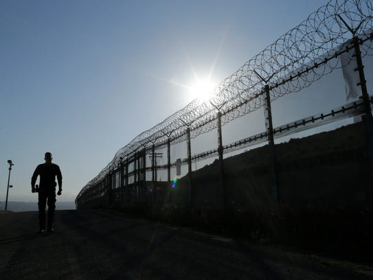 A Border Patrol agent walks along a border structure