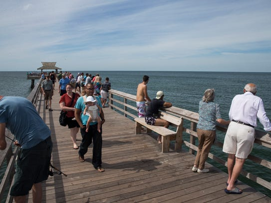 People walk and fish along the pier in downtown Naples
