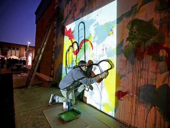 Aritist Irineo Medina works on a mural just off Wisconsin