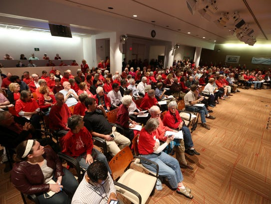 People listen in at City Hall during a meeting on Feb.
