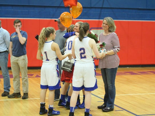 Senior Carrie Maney receives gifts from teammates Bailey