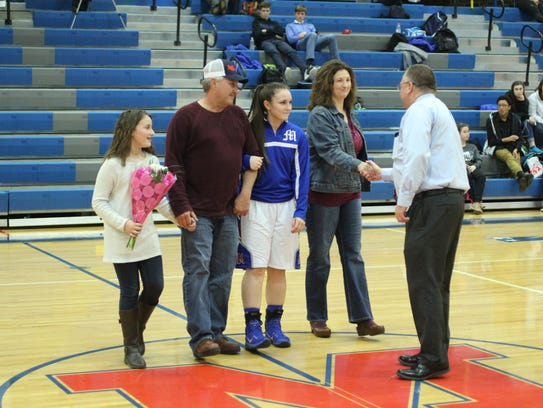 Senior basketball player Hollie Shelton accepts congratulations