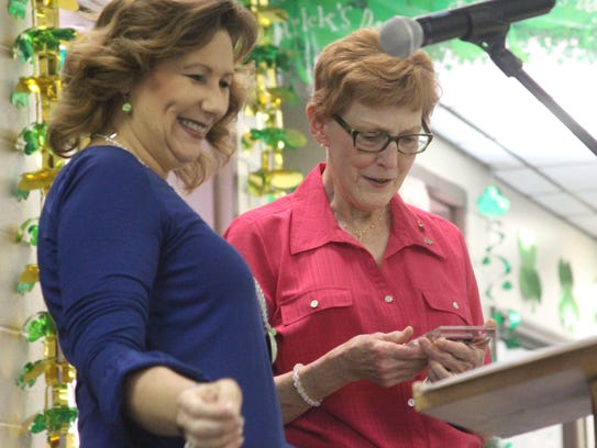 Joyce Pryor, right, looks at her Emerald Award, which