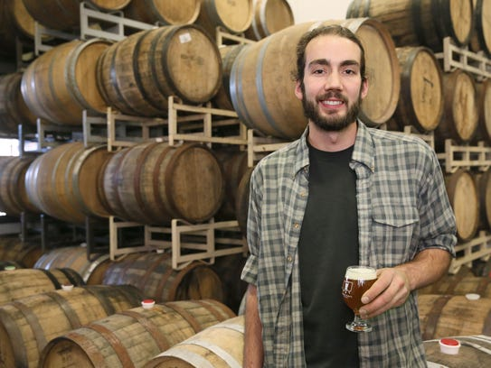 Brewer Adam Thomas raises a glass of sour beer at MboCraft,