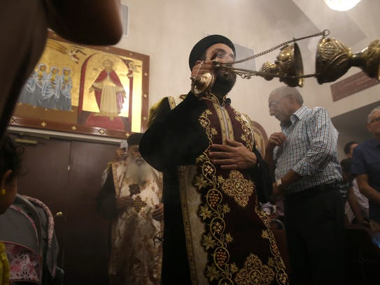 Father Jerome uses a thurible to surround parishioners