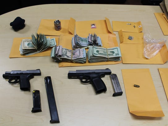 Police found two hand guns and nearly $20,000 in a