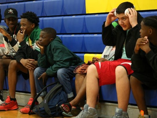 James Mambo, 14, sits with classmates during gym class
