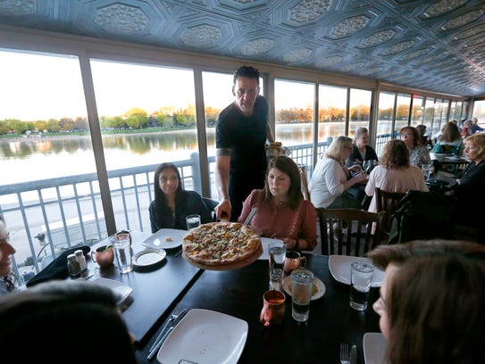 Server Henry Avignon brings a Massimo pizza to the
