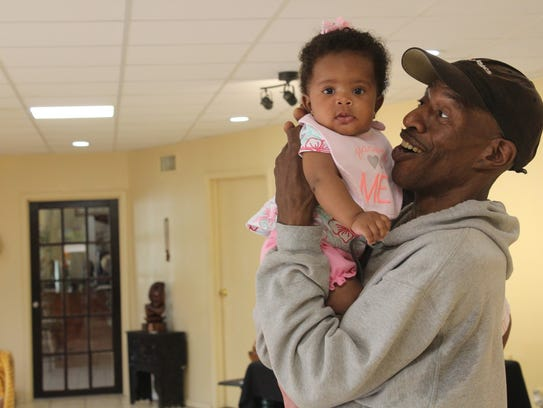 Rickey Lee holds his 4-month-old daughter Zera in the