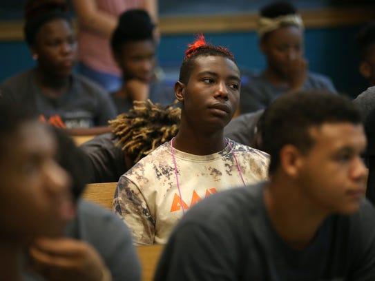 Trayver Johnson, 18, listens during a presentation