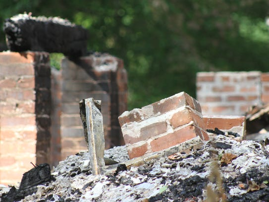 A charred wooden beam still stands atop brick foundation