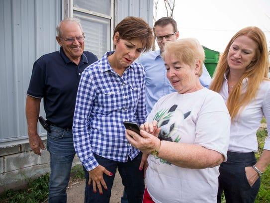 Gov. Kim Reynolds looks at storm photos on the phone