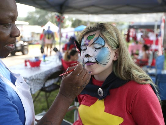 Lilliana Wimberley, 12, has her face painted by Rosetta